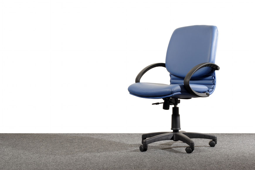 A blue office chair sits on grey industrial carpet and a blank white background