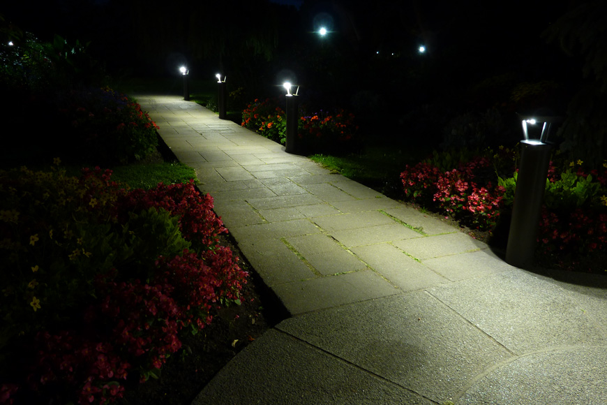 A series of solar lighting bollards illuminates a pathway edged in red flowers