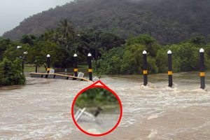 An image shows a bollard light tipped toward the receding floodwaters.