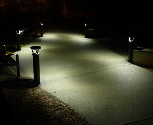Solar bollards illuminate a sidewalk at night