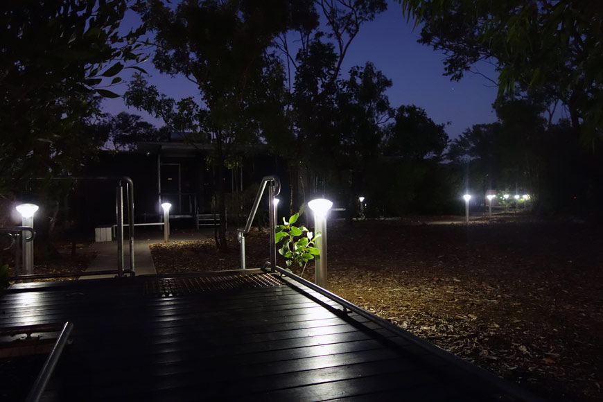 Glowing lights dot the edge of a pathway at night