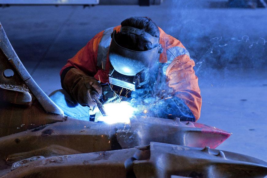 une personne qui porte un masque de soudeur travail sur un pièce de métal