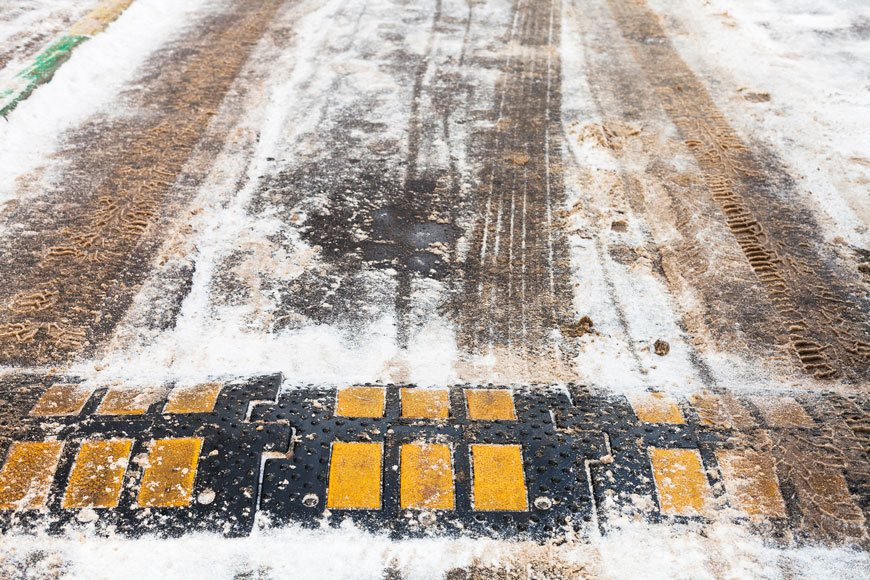 A speed bump is partially covered in the snow