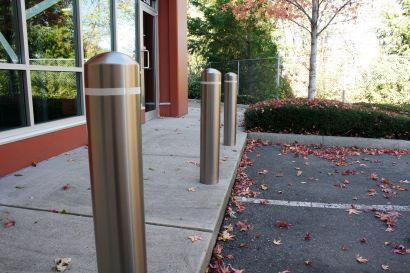 Three stainless steel bollard covers with reflective tape protect between sidewalk and parking lot