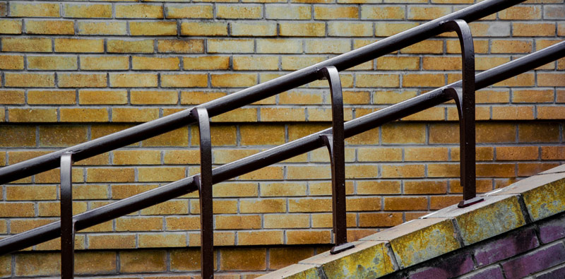 A brown powder-coated railing made of brown square and round tubing before a yellow brick wall