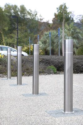 sleek stainless steel bollards block a stonework pathway