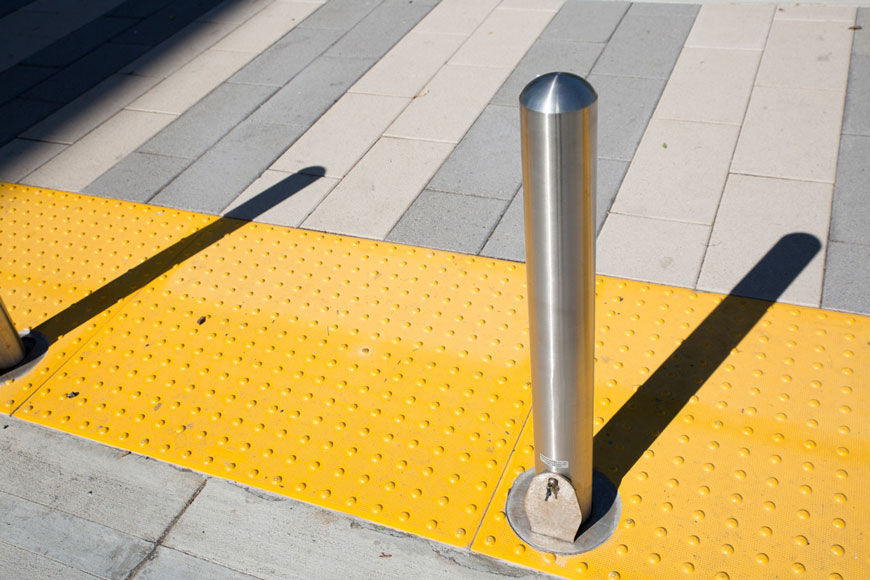 A stainless steel removable bollard is embedded next to yellow detectable warning plates
