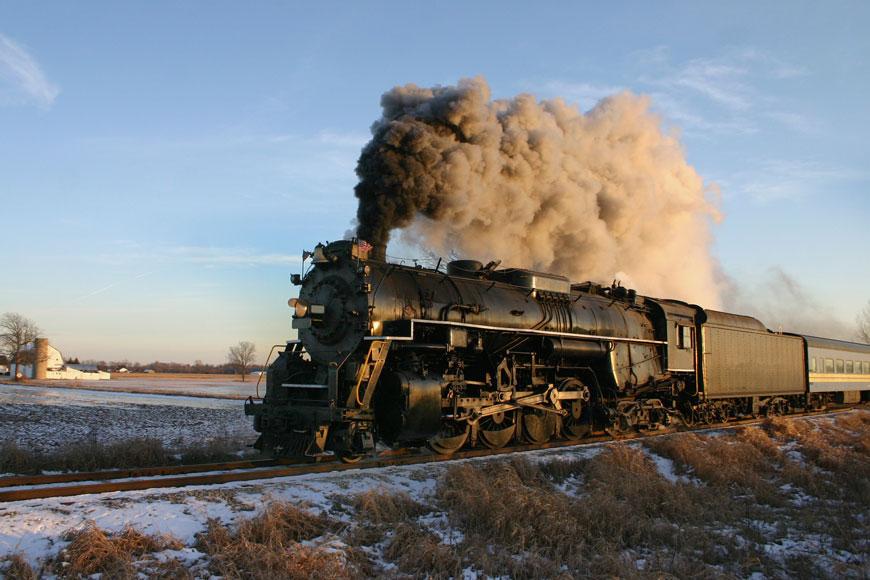 A steam locomotive belching black smoke trundles across a prairie on single-flanged steel wheels