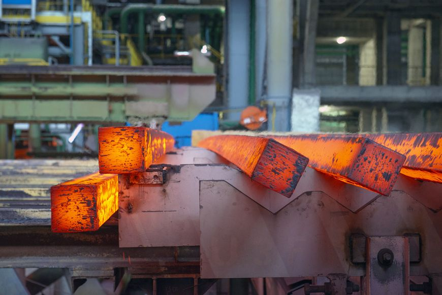 Close up of glowing bars of steel cooling in a steel mill