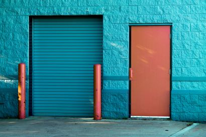 Two red bollards against a blue wall