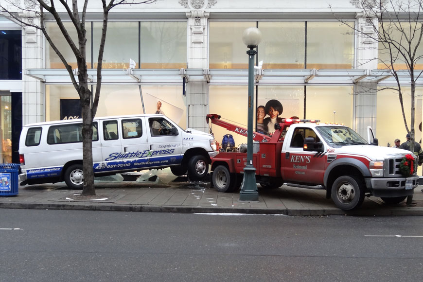 A tow truck pulls a bus-like shuttle out of the wreckage of a Gap store display