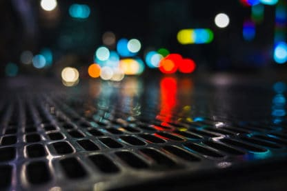 A closeup shot of a wet storm drain grate at night, black but reflecting lights in the background