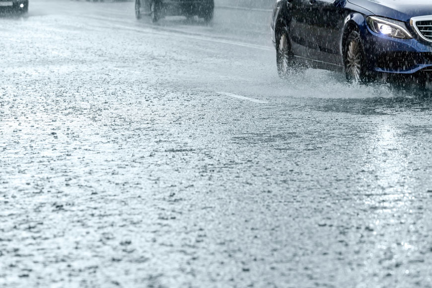 A car splashes through water accumulating on a road surface during a flash flood