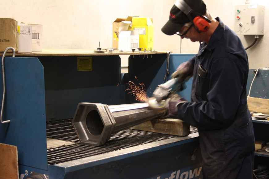 Sparks fly from a grinder wheel as a steel surface is machined smooth