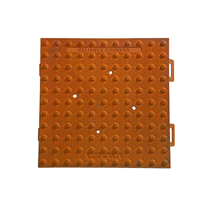 A raw cast iron square of tactile paving that's developed a red-brown rusty patina