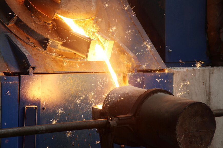 Molten metal being tapped out of an induction furnace into a pouring ladle