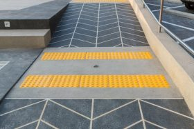 Two strips of tactile paving at the bottom of a two- directional ramp warn of changes in both directions.
