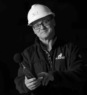 A smiling man in a hardhat and glasses holds an audio tester in a black and white photograph no caption