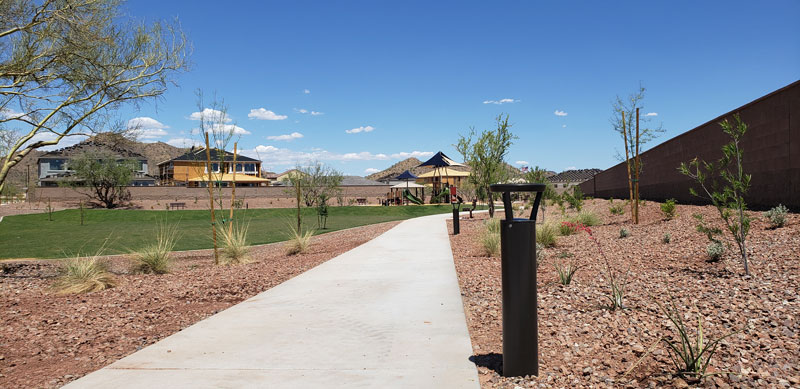 A scrubby southern landscape with a path between homes features black R-9811 solar bollards with lights