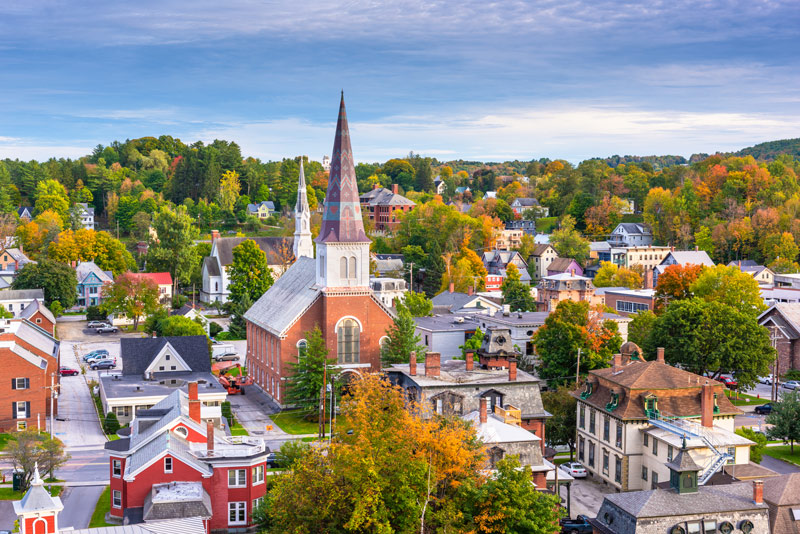 A town in Vermont in autumn populated with red, orange, and yellow trees
