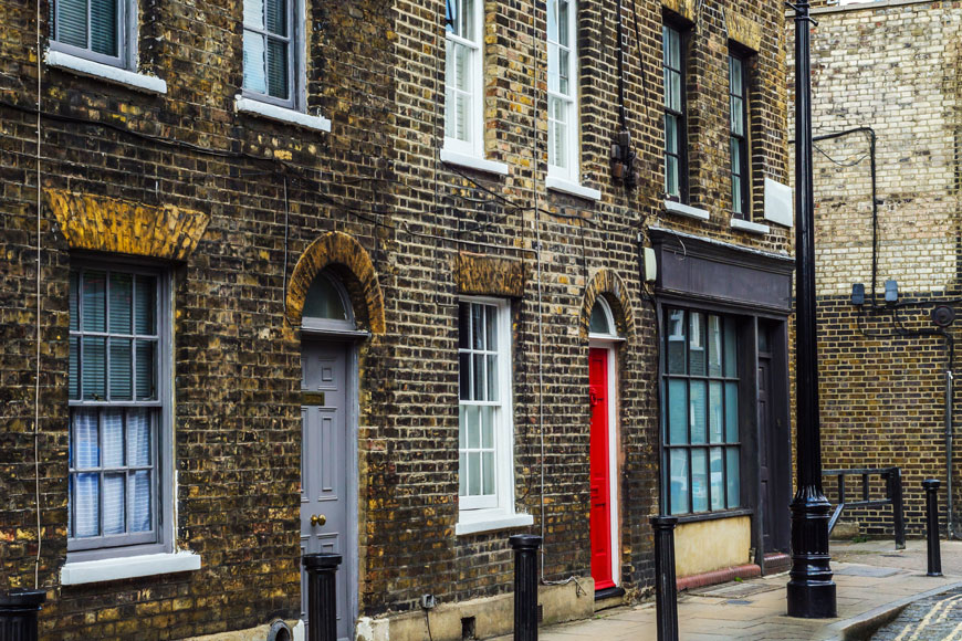 A series of brick rowhouses on an Old London street