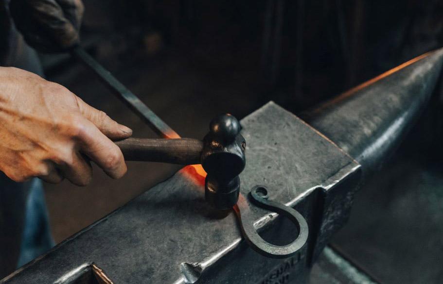 A blacksmith forges a decorative hook