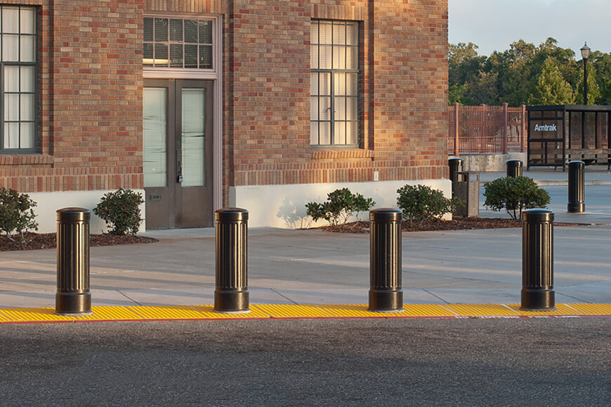 Four bollards in a line protect pedestrians from accidental contact