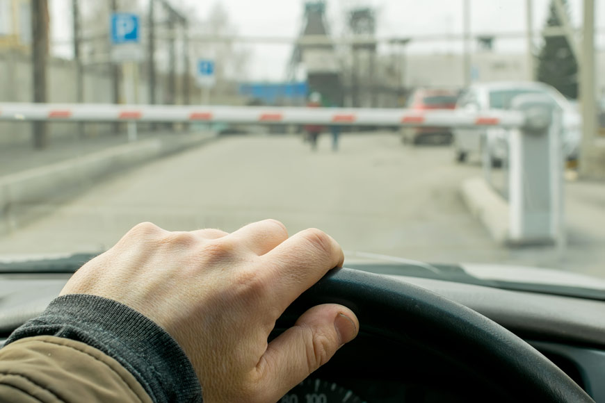 A man's hand on a steering wheel as he drives into a parking lot