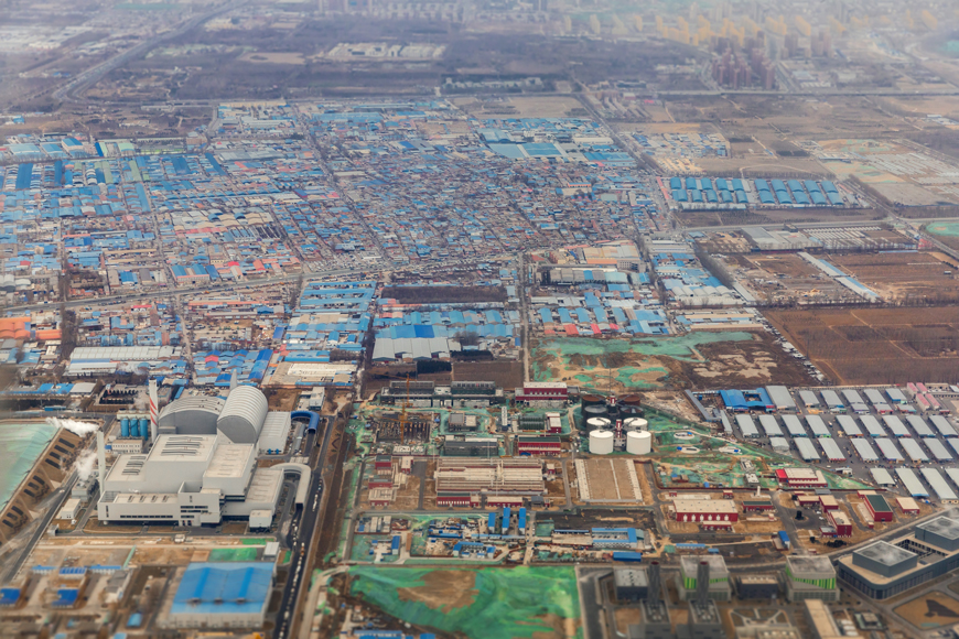Blue roofed buildings and several large warehouses dominate an aerial view of an industrial area.