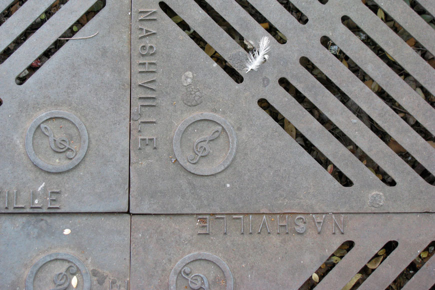 A close shot of four adjacent tree grates branded Nashville featuring a white feather stuck in one corner