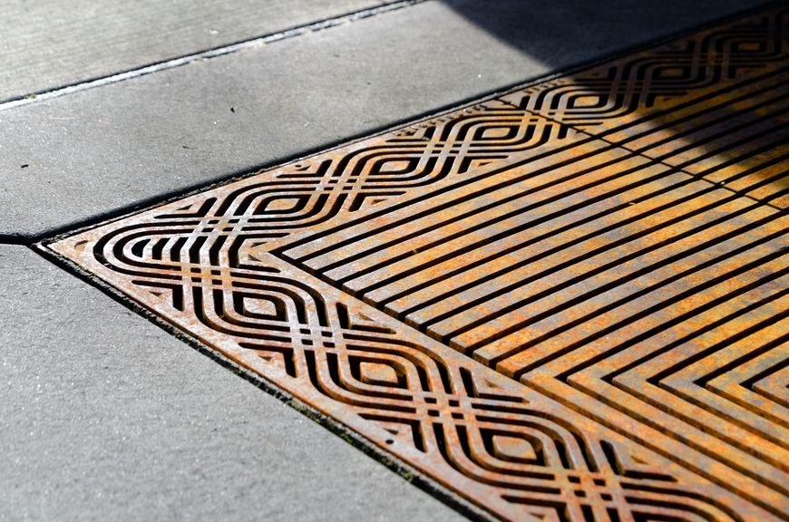 Raw cast iron tree grate with an oscillating edge pattern