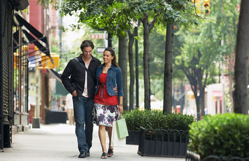 A young couple walks in NYC past sidewalk trees surrounded by short box hedges and black decorative fences