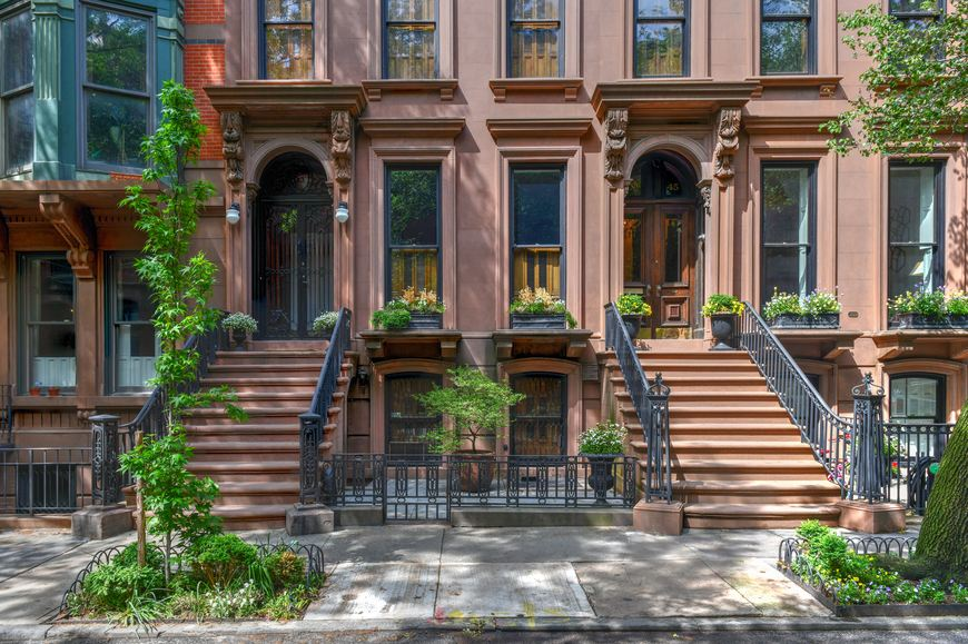 Traditional New York brownstones are framed by two small trees in tree pits on the sidewalk.