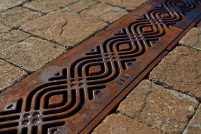 Water soaks into a decorative cast iron grate red and brown with developing patina