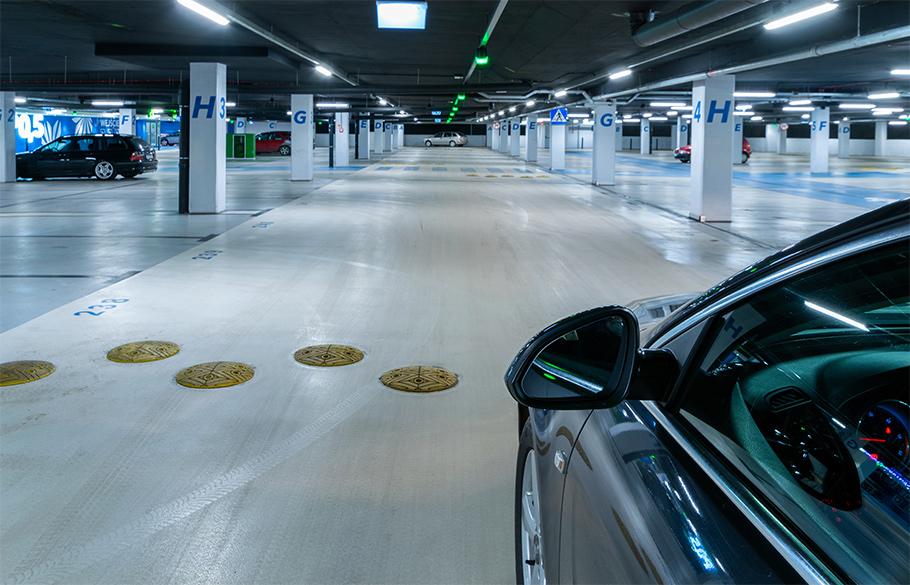 A black car maneuvering through an underground parking lot