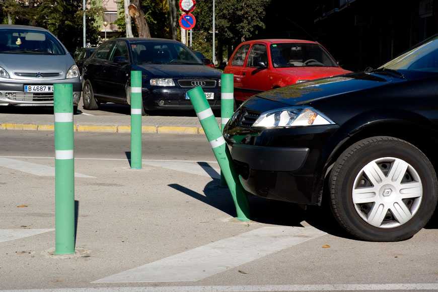 A green bollard with white reflective tape bends under the force of a car's bumper