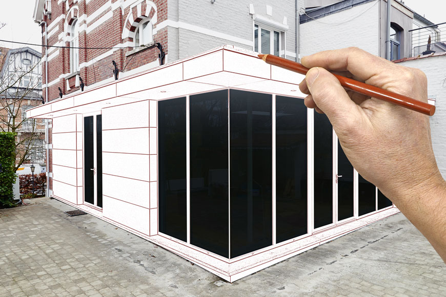 An architect's hand sketches a new addition onto a picture of a historic building