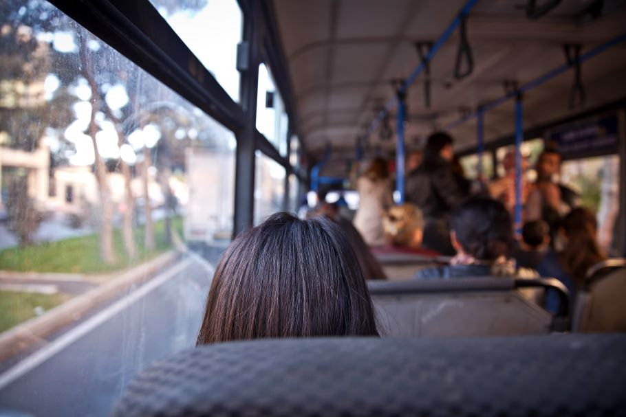 A woman sits on a bus: we see the back of her head as she looks out the window. People stand near the front of the bus.