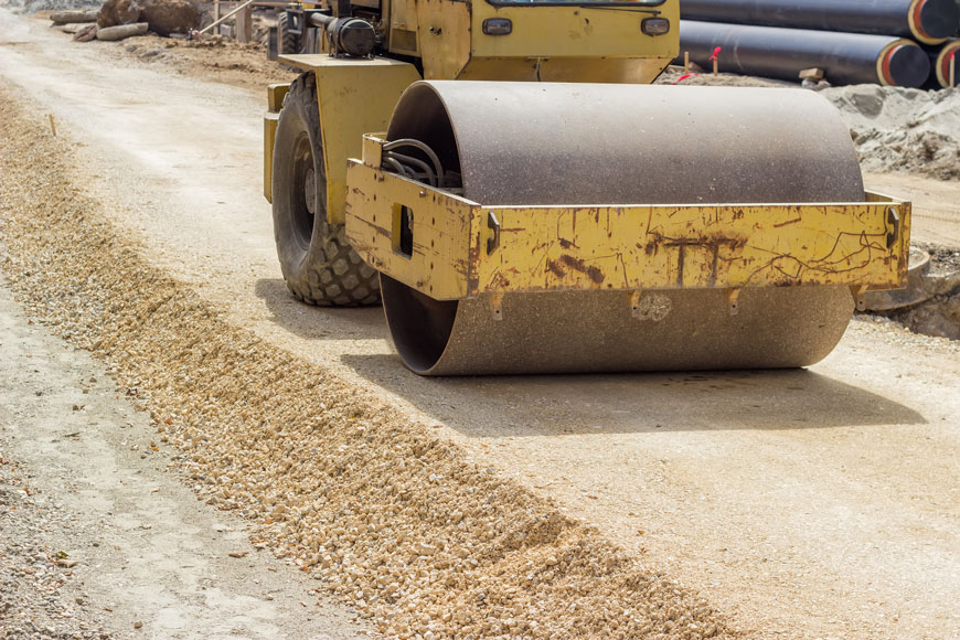 A vibratory steel drum compactor is used to damp down sand as a road base