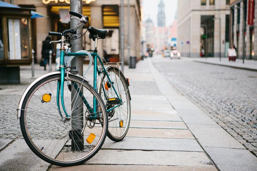 Vélo bleu verrouillé sur un poteau en métal avec un câble antivol dans une rue européenne