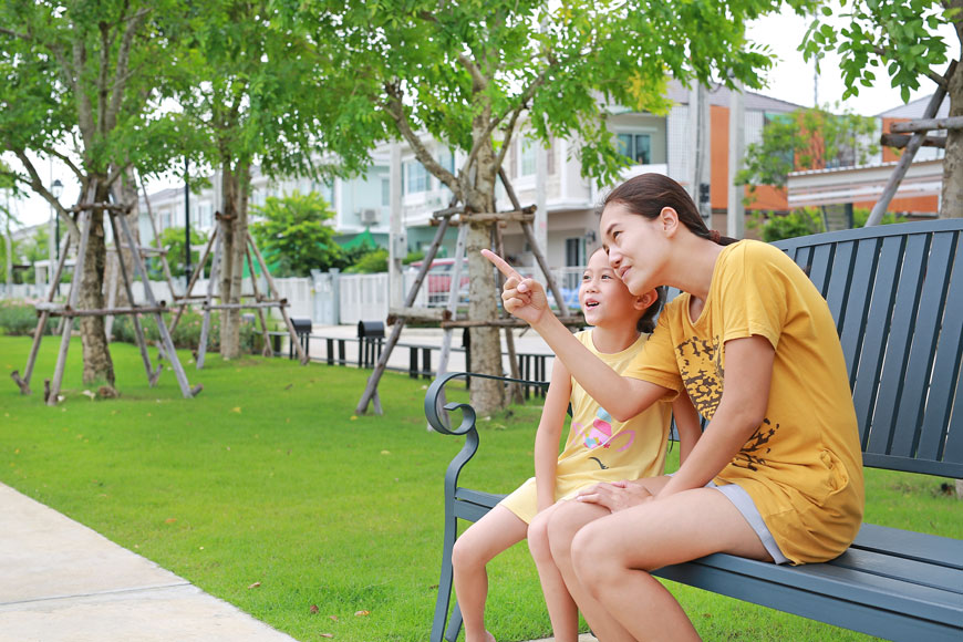A mom and child sit on a park bench looking at a view, braced trees behind them.
