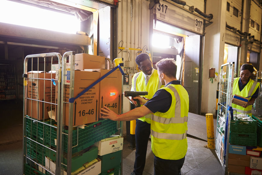 Workers fill a truck in a loading bay protected by warehouse bollards
