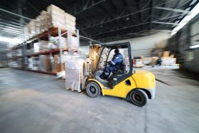 A yellow seated forklift carries a pallet to a line of shelving.