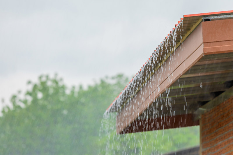 Rain water pours over the edge of a tile roof