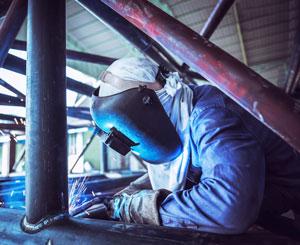 Welder works on steel pipe