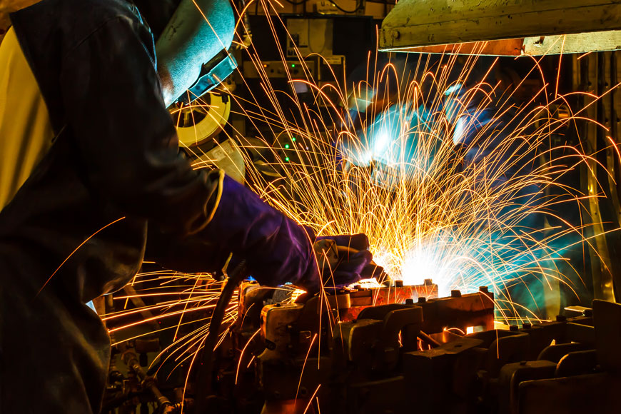 In a picture of colorful contrasts, a welder creates a bloom of sparks with his torch on an automotive casting