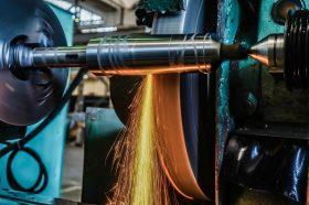 A circular grinder machines a high-precision steel part