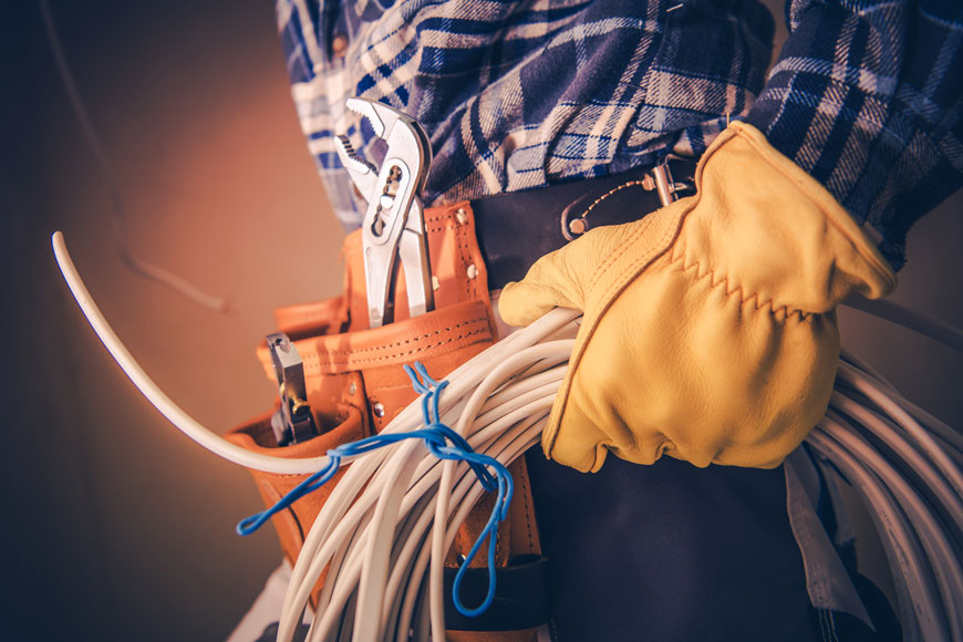 A close body studio shot of an electrician holding a loop of wire and wearing electrician's belt